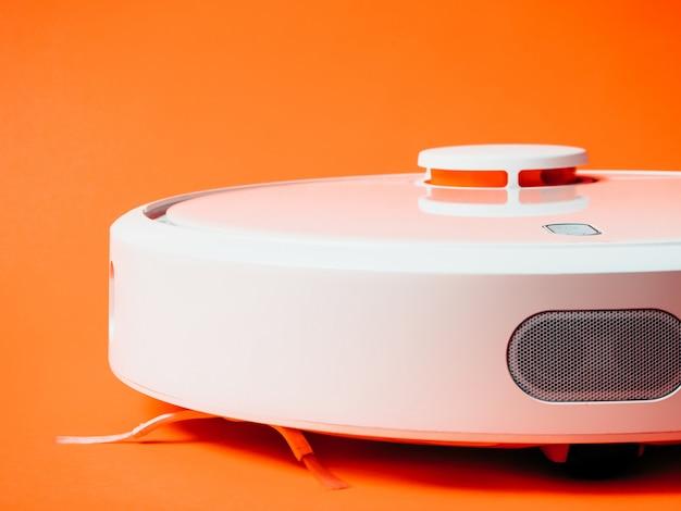 オレンジ色の背景に分離された白いロボット掃除機。