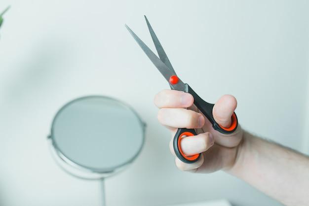 Мужская рука с ножницами напротив зеркала. остаться дома.