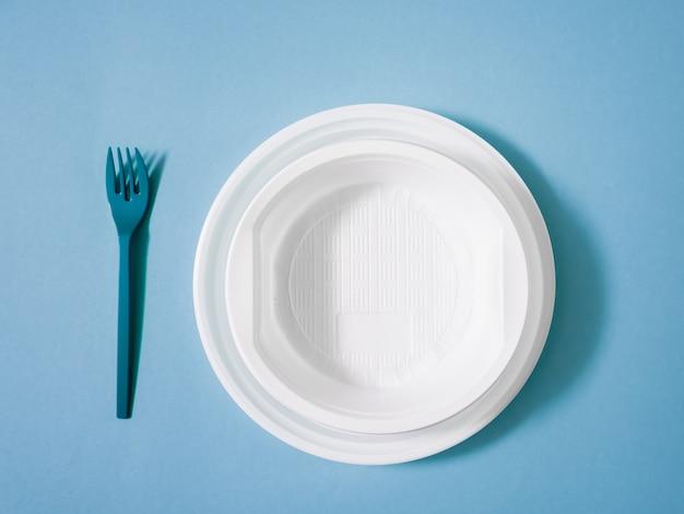 プラスチック製の食器、使い捨て食器、プレート、グラス、スプーン、青色の背景にフォーク。環境への配慮。問題はリサイクルです。再利用、安全な惑星、環境コンセプト。ゴミ。