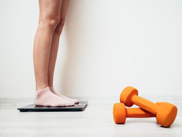 靴下の女性の脚は、白い壁に電気スケールで立っています。近くにはフィットネス用のオレンジ色のダンベルがあります。減量の概念。