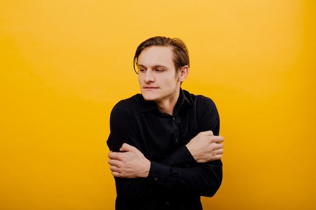 男は寒い、スタジオ、黄色の背景