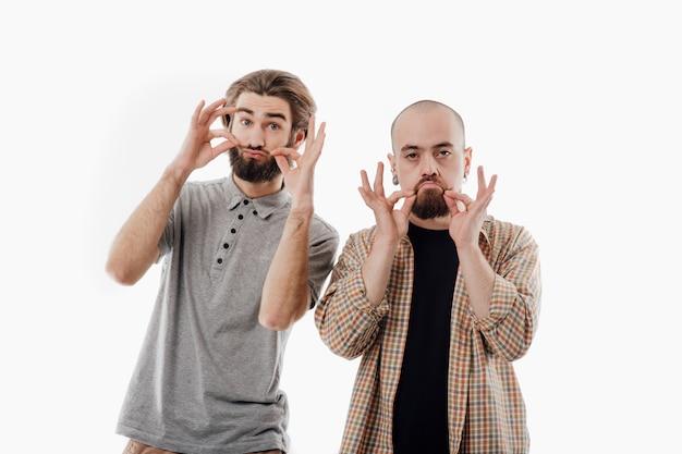 Двое мужчин гримасничают с усами, изолированное белое пространство, копией пространства