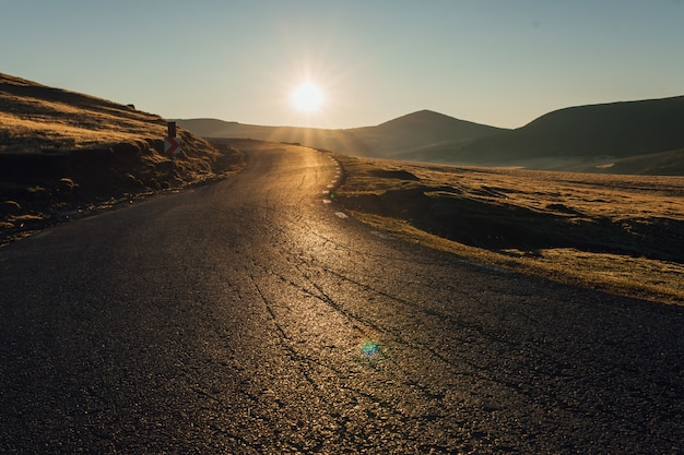 風景シーンと道路、ルーマニアの上の日の出
