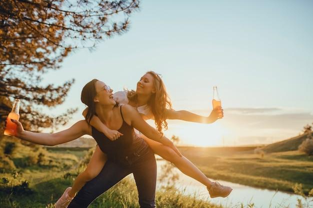 Девушки в солнечных очках весело проводят время с коктейлями на закате, летом, теплыми эмоциями, позитивным выражением лица, отдыхом, отдыхом и счастьем.