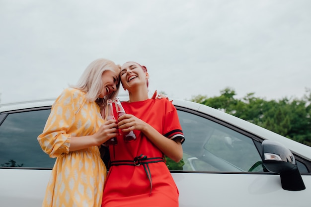 車の横にボトルドリンクを飲みながら二人の若い女の子