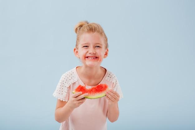 スイカのスライスを食べるかわいい女の子