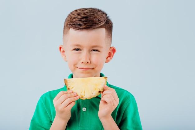 パイナップルスライスを食べるかわいい男の子