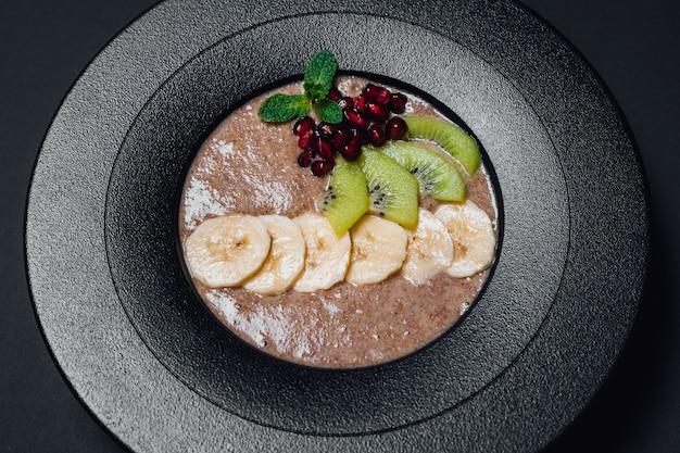 Веганская каша. в обезвоженном, растительном молоке, банане, меде, киви, гранате. на тарелке, изолированные на черном фоне, крупный план, вид сверху