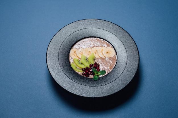 Веганская каша. в обезвоженном, растительном молоке, банане, меде, киви, гранате. на тарелке, изолированные на синем фоне, крупный план, вид сверху