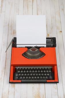 白い木製の背景に赤のタイプライター