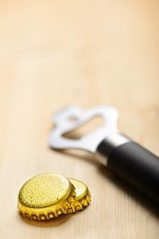Две металлические пивные крышки бутылки и открывалка на деревянный стол