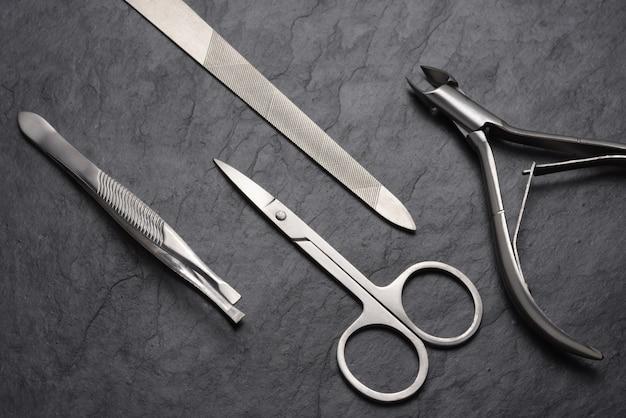 Маникюрный и педикюрный набор инструментов и аксессуаров на черном фоне