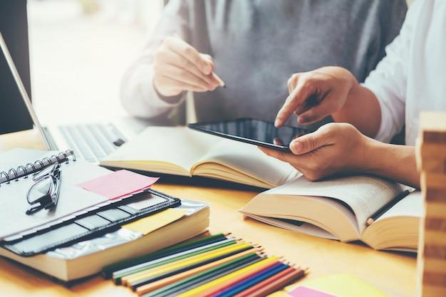 Средние школы или студенты колледжа, изучающие и читающие вместе в библиотеке
