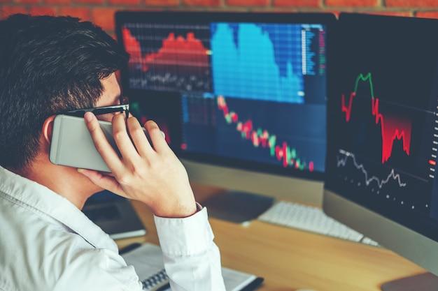 ビジネスマンがオンラインで取引する携帯電話を使って投資を議論する
