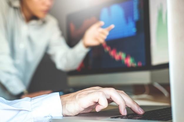 ビジネスチームの取引株オンライン投資議論と分析グラフの株式市場