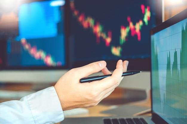 ビジネスマンの株式をオンラインで取引投資の議論と分析グラフの株式市場