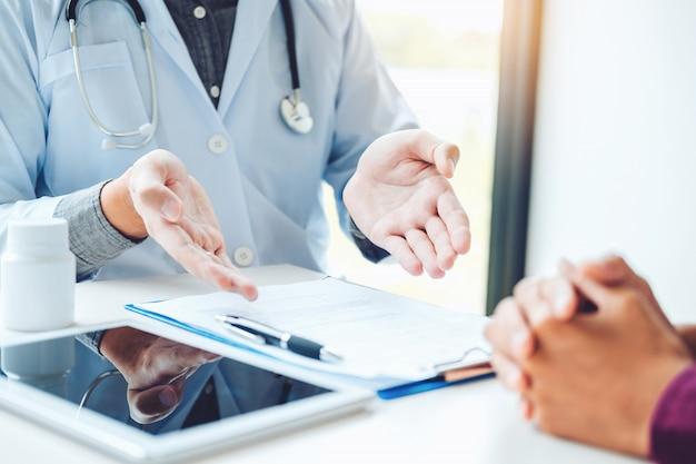 医者と患者は座って話します。病院の窓の近くのテーブルで。