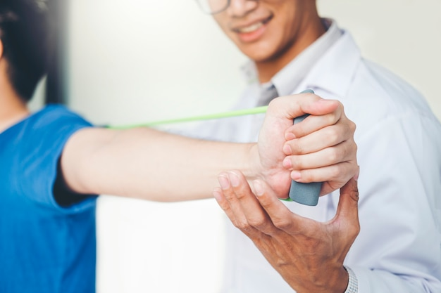 抵抗バンド運動治療を与える理学療法士男腕と肩について