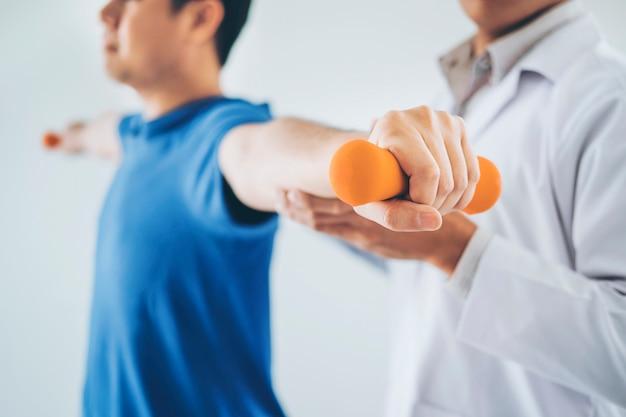 Физиотерапевт мужчина делает упражнения с гантелями лечения о руке и плече