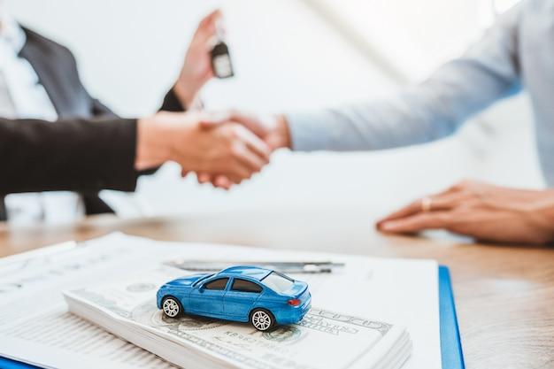顧客との成功した自動車ローン契約に合意し、契約契約に署名する販売代理店ハンドシェイク契約保険車。