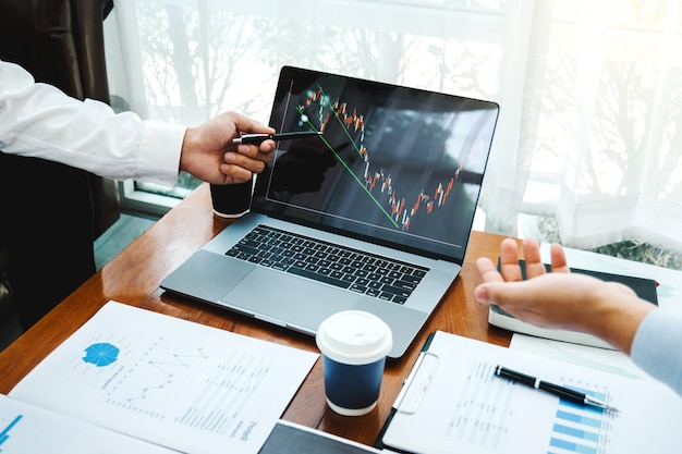ビジネスチーム投資起業家トレーディングディスカッションと分析グラフ株式市場取引
