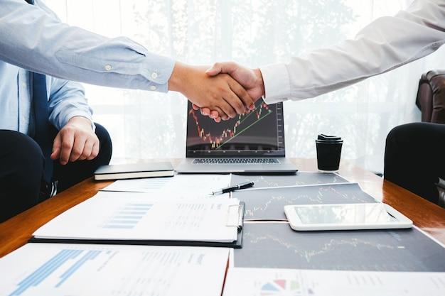 Бизнес-команда, обменивающаяся рукопожатием с инвестиционным предпринимателем, обсуждающим и анализирующим график торговли на фондовом рынке, концепцию биржевого графика