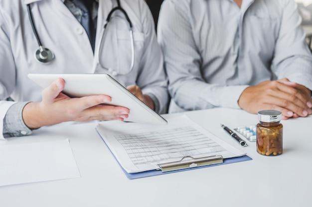 Доктор, консультации с пациентом, представляя результаты на цифровой планшетный планшет, сидя за столом