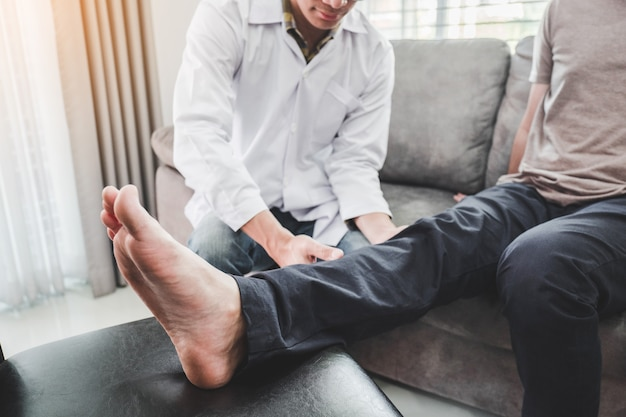 Физический врач, консультирующийся с пациентом проблемы с коленом физиотерапия посещение дома пациента