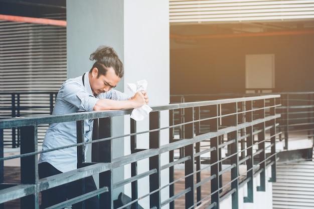Усталый или подчеркнул бизнесмен, стоя на дорожке после работы подчеркнул концепции бизнесмена