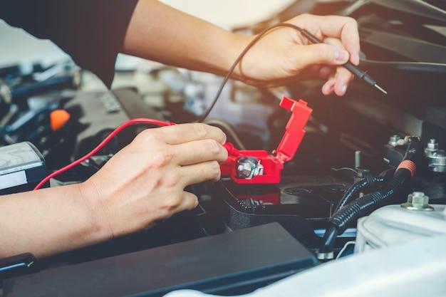 手は自動車修理サービスで働くバッテリー自動車のメカニックをチェックする