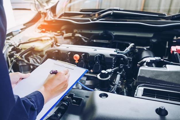 ガレージで働くサービスオーダーのクリップボードを持っている機械工。修理サービス。