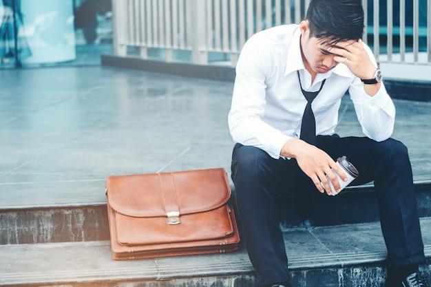 Усталый или подчеркнул бизнесмен, сидя на дорожке после работы на открытом воздухе концепции