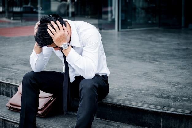 Безработный устав или стресс бизнесмен сидит на дорожке после работы