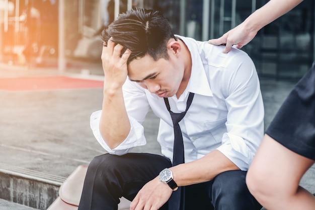 Усталый или подчеркнул бизнесмен, сидя на дорожке после работы