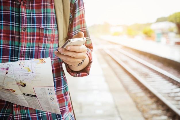 Молодой турист с бородой, держащей карту и использующей концепцию путешествий по мобильному телефону