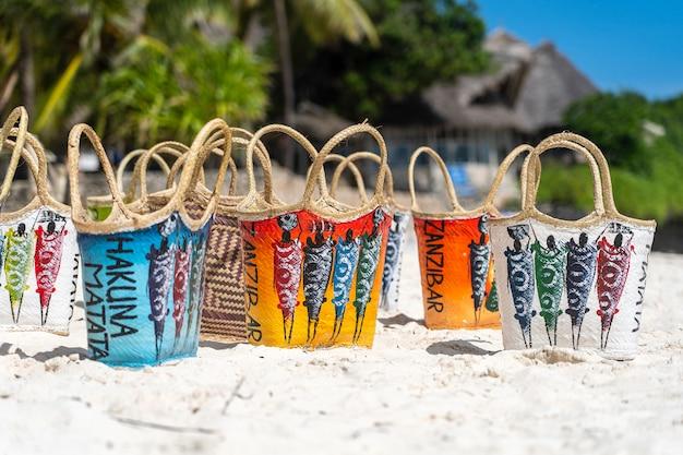 ザンジバル島のターコイズブルーの海の近くの白い砂浜で典型的なザンジバルスタイルの着色された枝編み細工品女性バッグ
