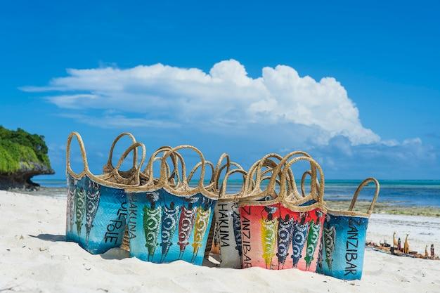 ザンジバル島、タンザニア、東アフリカのターコイズブルーの海の近くの白い砂浜で典型的なザンジバルスタイルの色の枝編み細工品女性バッグをクローズアップ