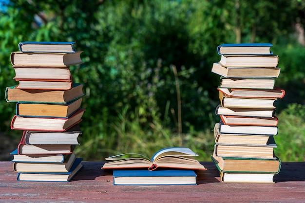 自然の上の木製のテーブルの上の本のスタック