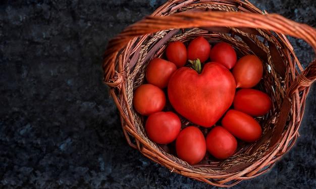 Помидоры в плетеной корзине. один большой помидор в форме сердца, окруженный маленькими помидорами черри