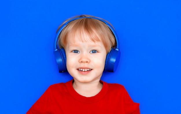 Ребенок мальчик на синем фоне в синих беспроводных наушниках радостно улыбается слушает