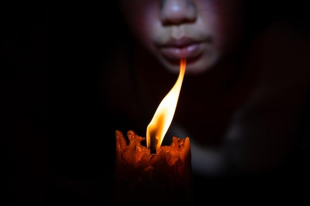 Лицо женщины, задуть свечу на черном