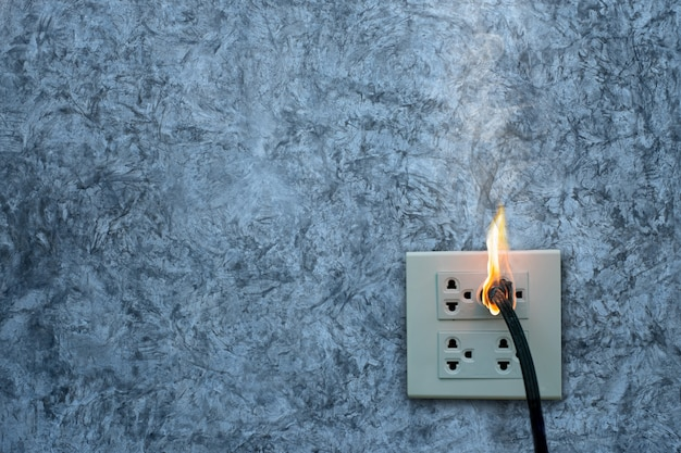 В огне электрическая вилка, розетка, на бетонной стене выставлен бетон