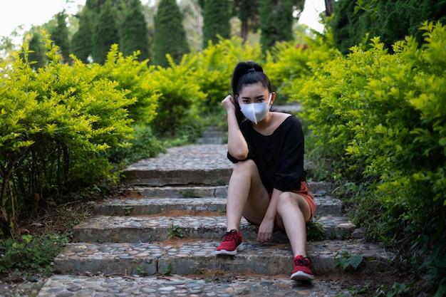 Молодая азиатская женщина сидит и надевает лицевую маску для защиты от респираторных заболеваний, передаваемых воздушно-капельным путем, как пыль гриппа и смог в парке, концепция вирусной инфекции безопасности женщин