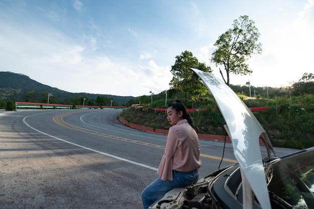 Молодая азиатская женщина сидит возле машины для вызова помощи на дороге общего пользования