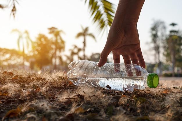 Крупным планом рука собирает прозрачную пластиковую бутылку с напитком с зеленой крышкой на дороге в парке на размытом фоне, мусор, который остается за пределами мусорного ведра
