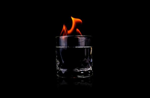 Стекло с водкой и пламенем огня на черной поверхности
