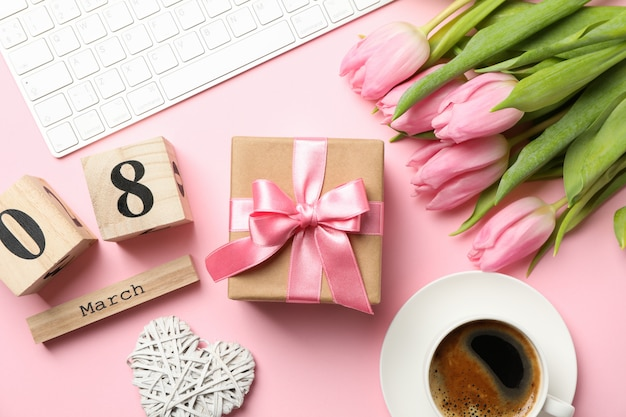 Композиция с тюльпанами и подарком на розовом, вид сверху