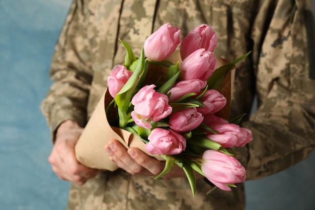 Человек в военной форме, держа букет тюльпанов на синем, крупным планом