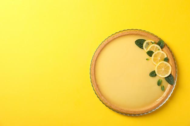 Стеклянный поднос с лимонным пирогом на желтом, вид сверху