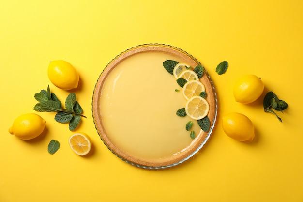 Лимонный пирог, мята и лимоны на желтом, вид сверху